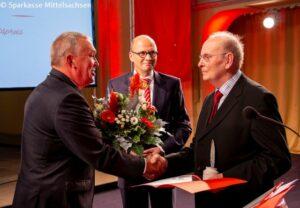 Volker Haupt vom Hilliger e. V. (li.) und Prof. Hans-Ferdinand Schramm, Vorstandsvorsitzender der Sparkasse Mittelsachsen (Bildmitte), gratulieren Herrn Dr. Rainer Thümmel zur Ehrung.